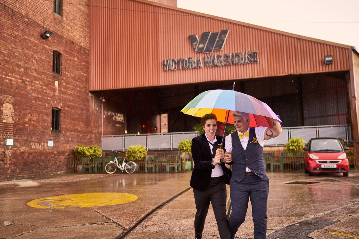 two Bride walking with rainbow umbrella in front of Victoria Warehouse