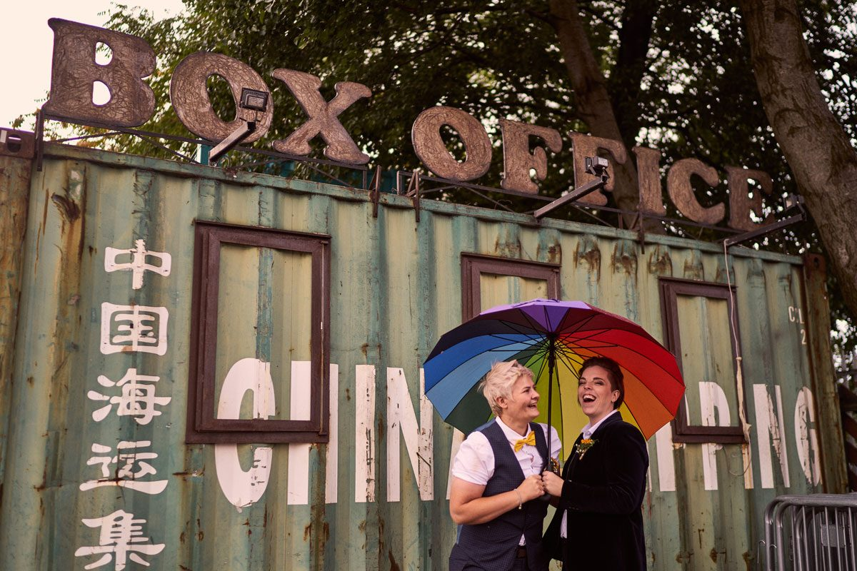 two brides laughing under a rainbow umbrella in the rain, outside Victoria warehouse