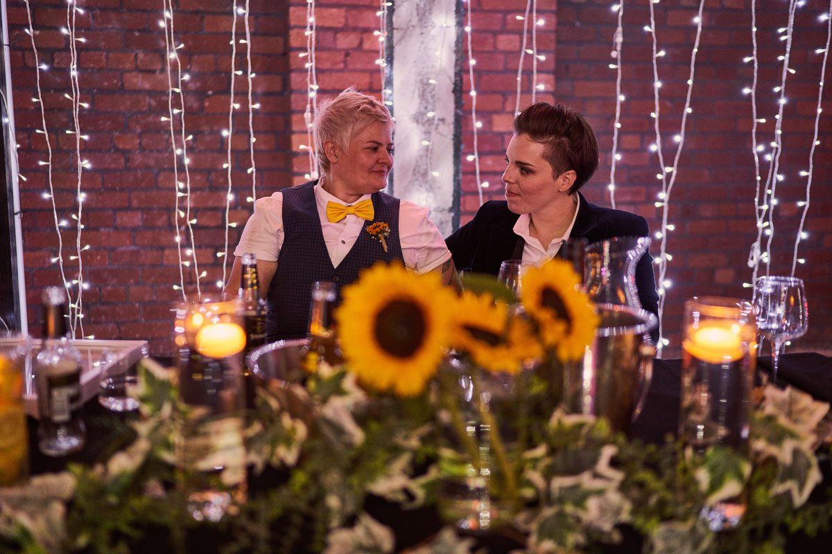 two brides look lovingly at each other during Bridesmaid speech