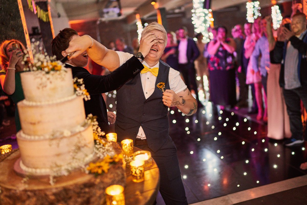 Brides smushing wedding cake into each others faces