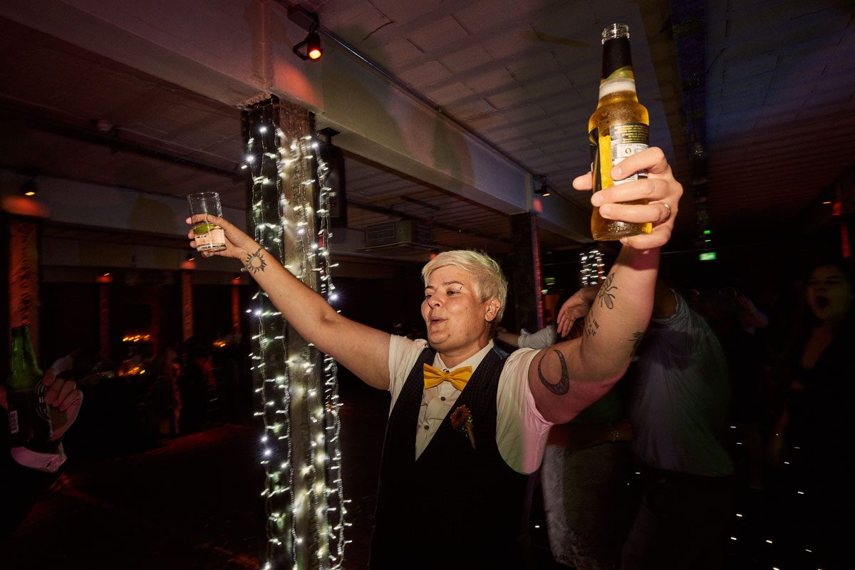 Bride with two drinks celebrating being married