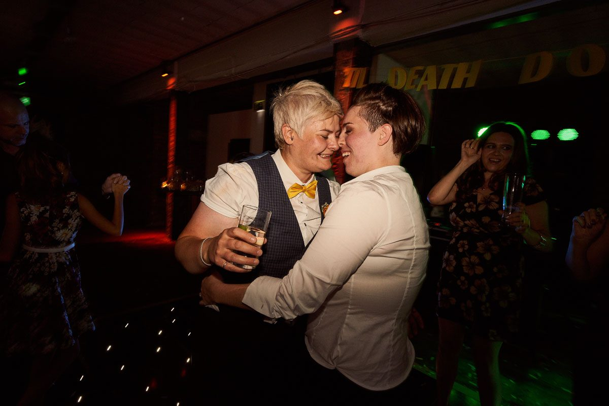 two brides embracing each other during last wedding dance