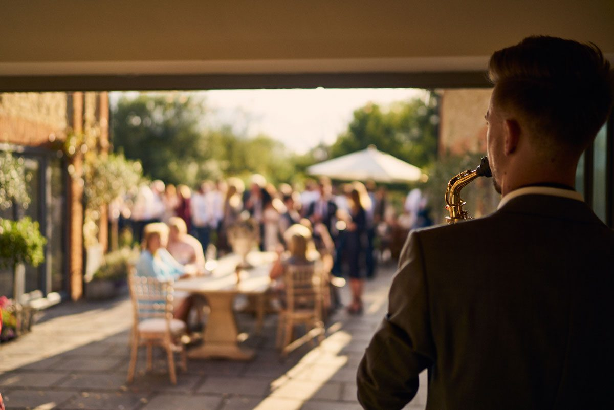 Dan Goode playing sax while wedding guests enjoy drinks on the terrace at Millbridge Court