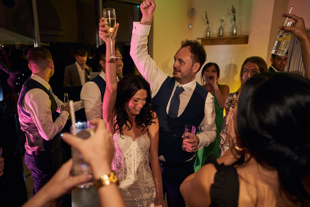 Bride & Groom raising their glasses and hands on the dance floor