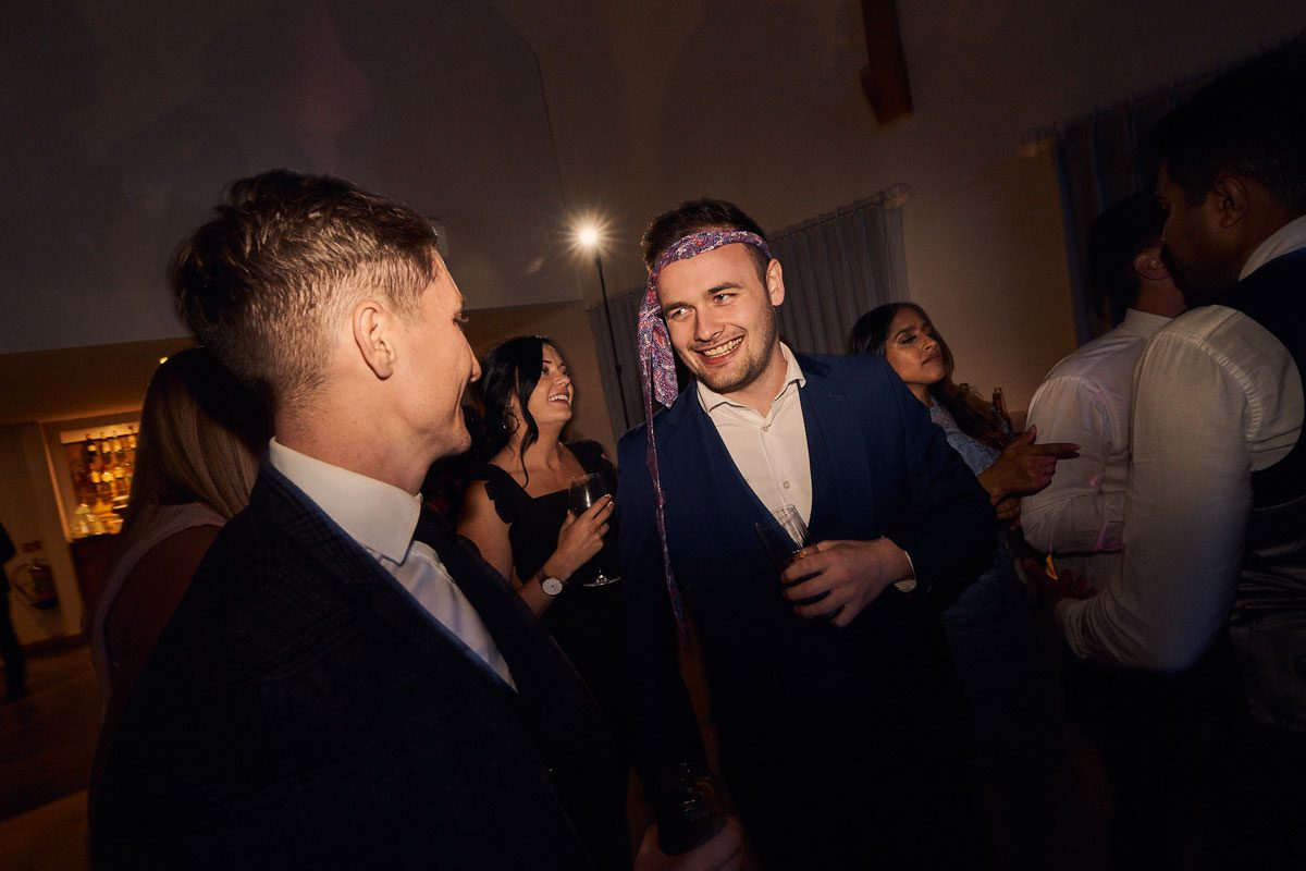 wedding guest with tie tied around his head