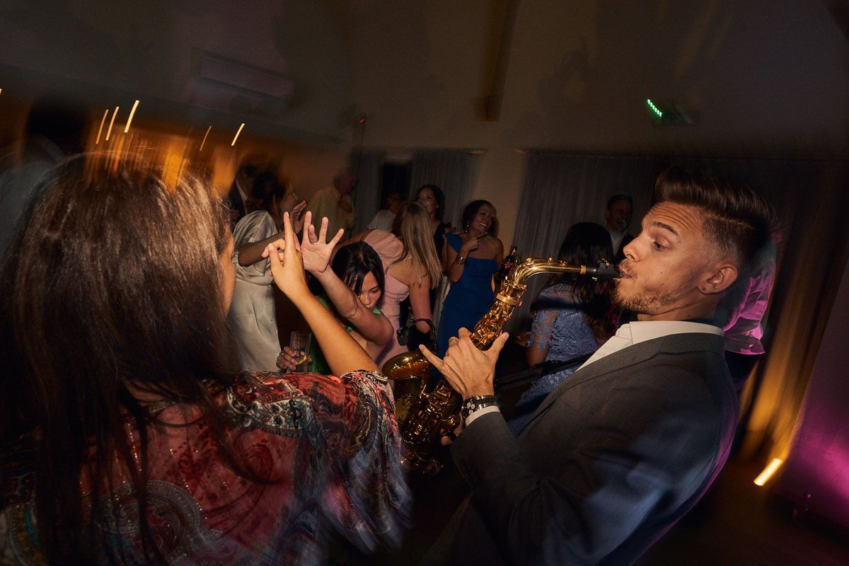 Dan Goode playing sax surrounded by wedding guests