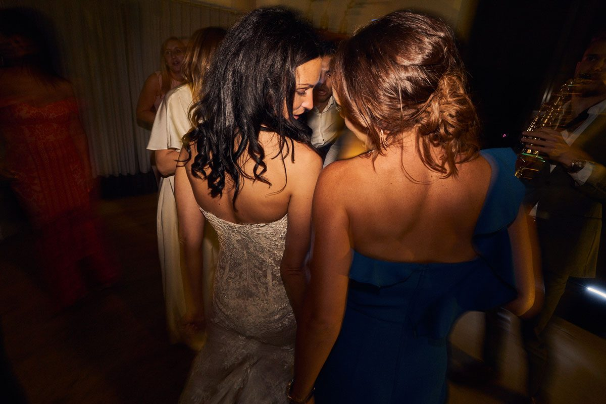 Bride and friend having a moment on the dance floor