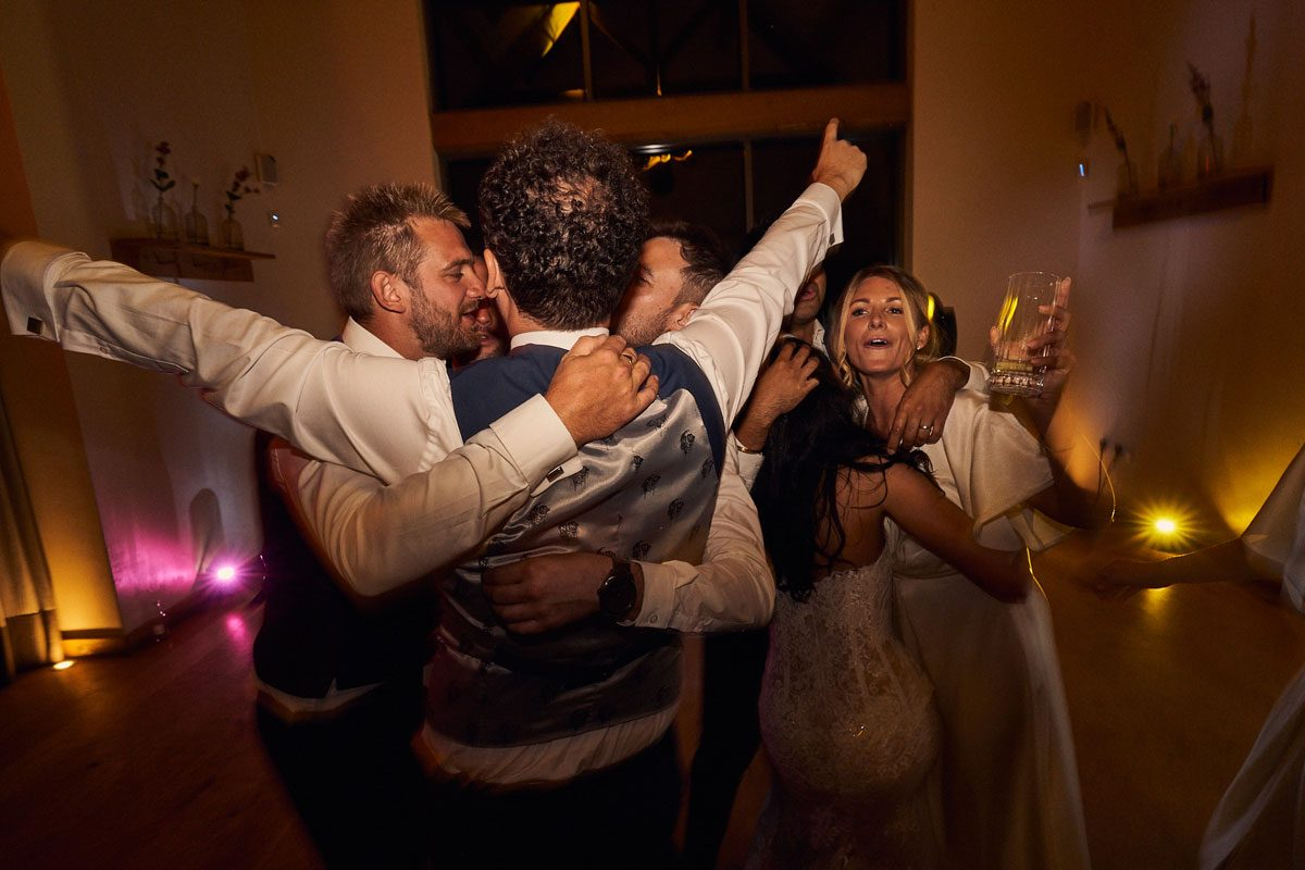 Groom hugging his mates towards the end of the night