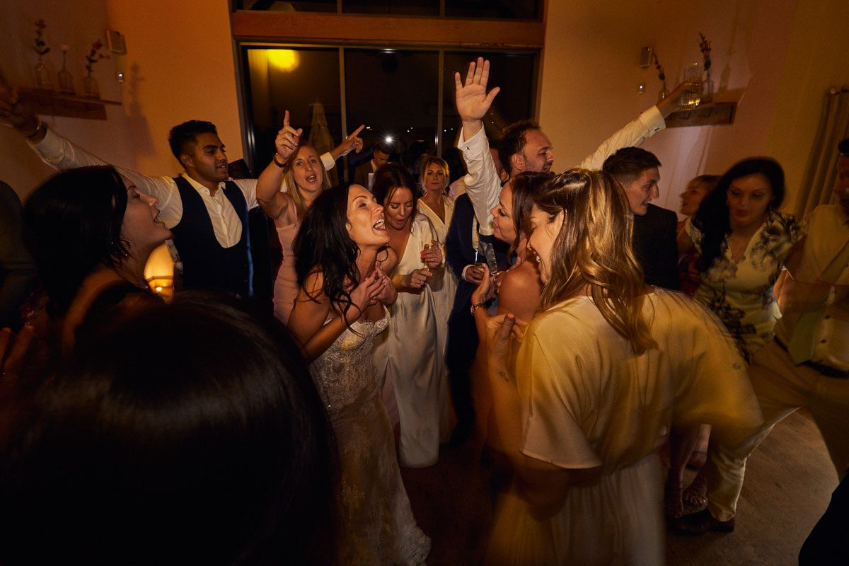 everyone surrounding Bride & Groom and singing along to the last song of the night