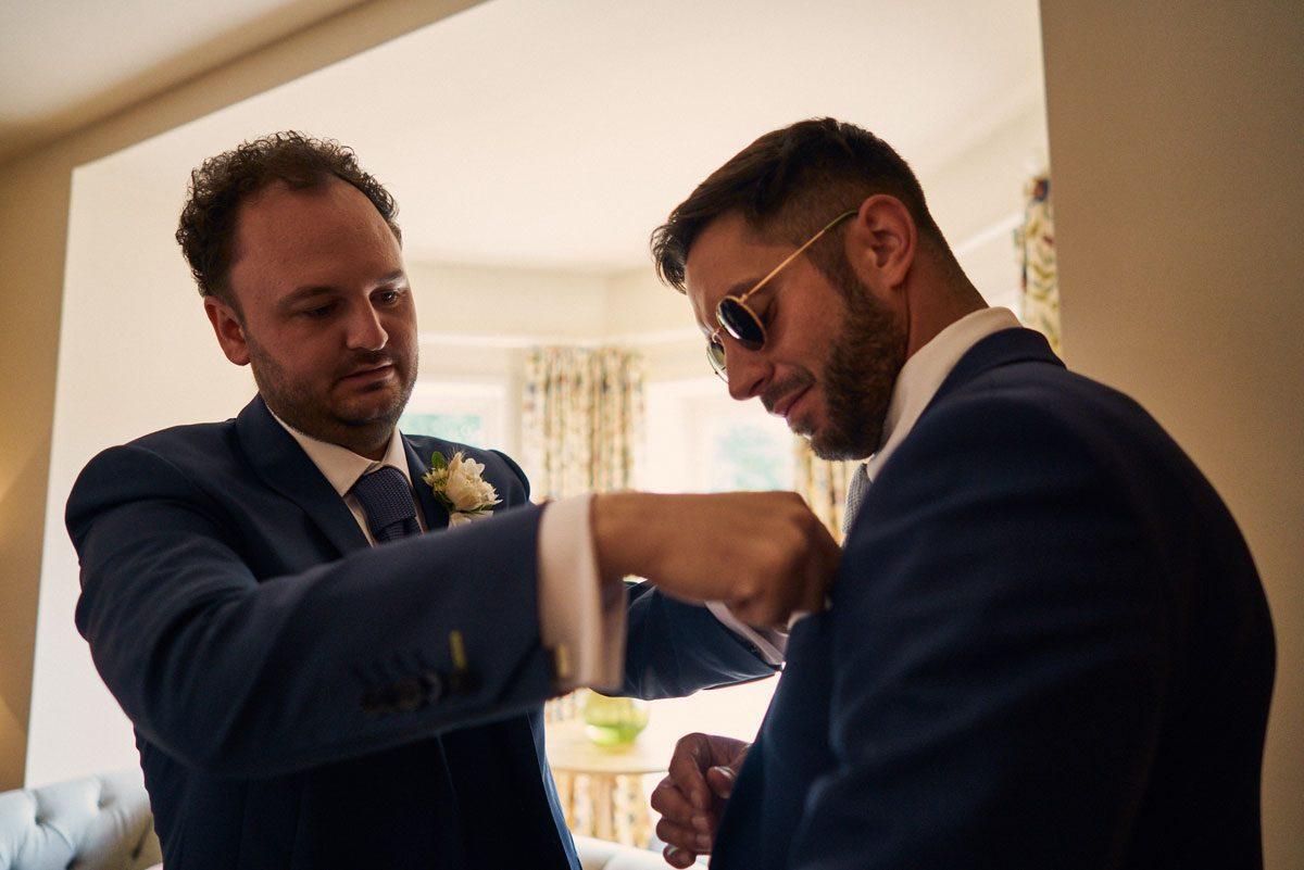 groom putting pocket square in Best Man's pocket