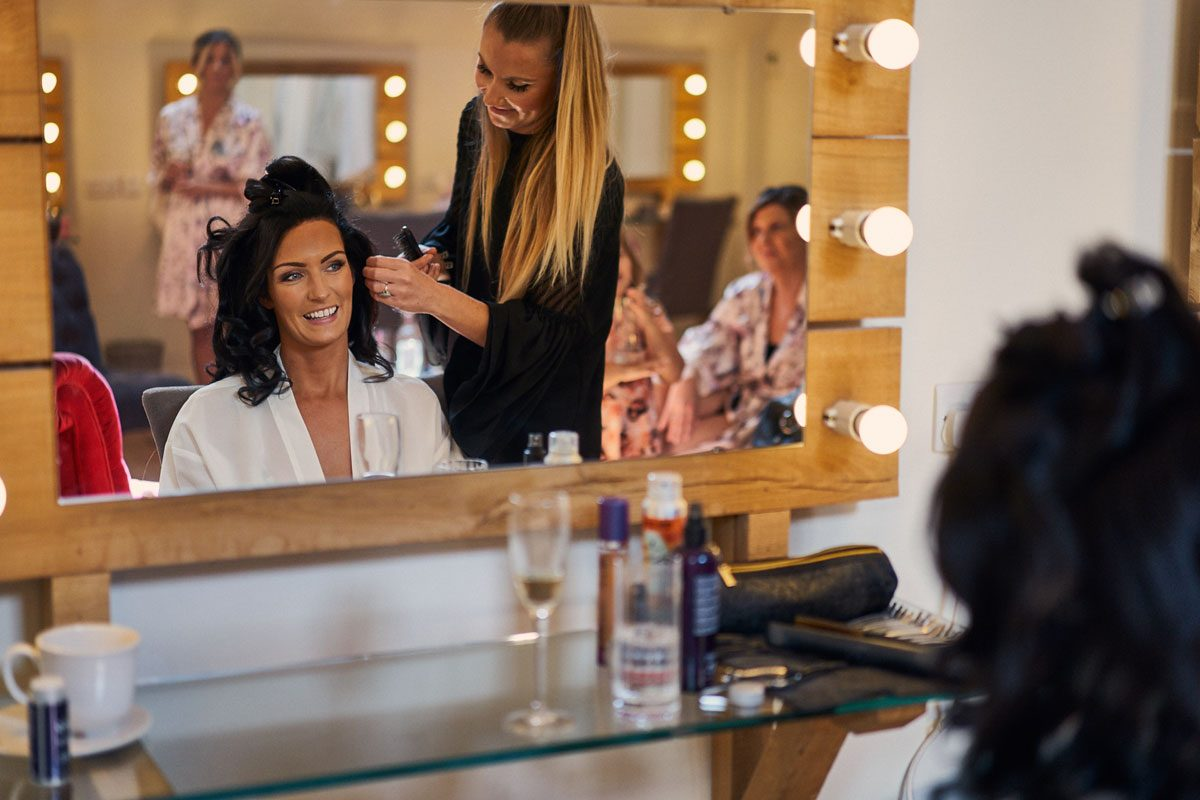 Bride smiling while having her hair done