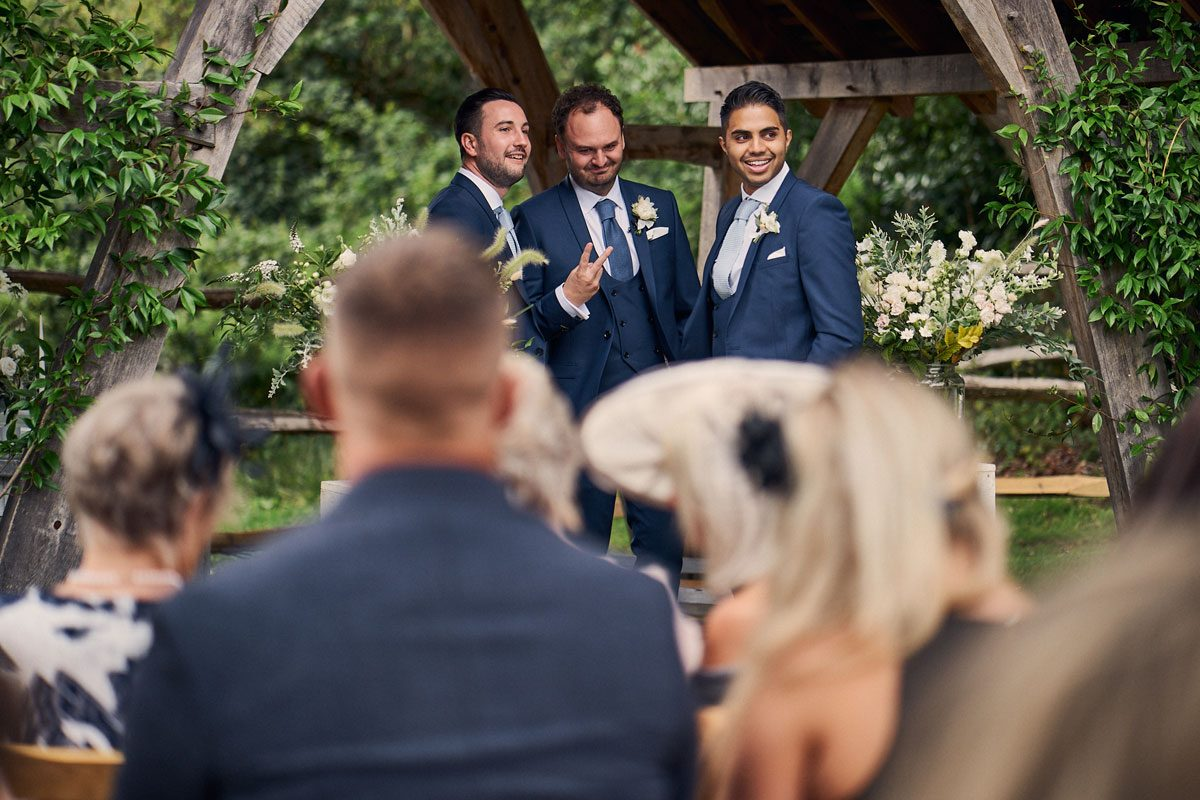 Groom sticking his fingers up at wedding guest