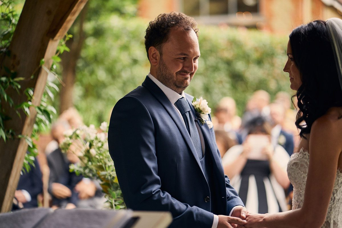 Groom smiling at Bride as they get married