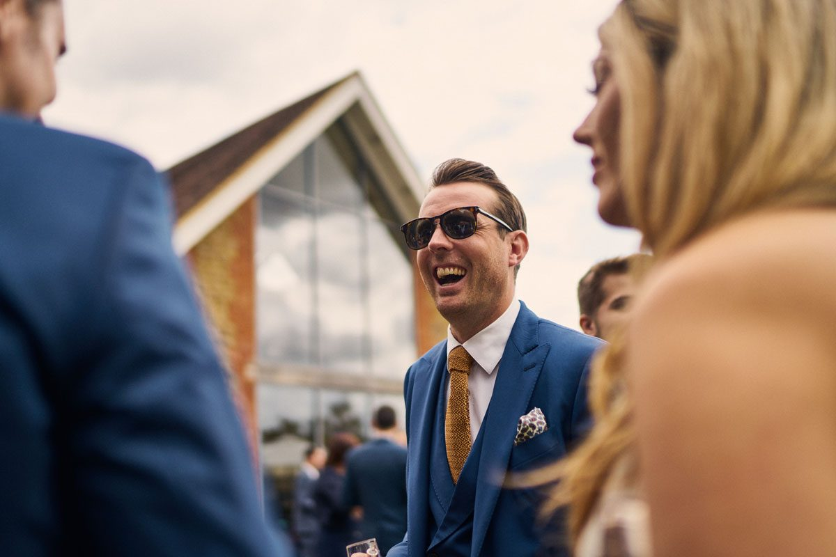 wedding guest smiling with sunglasses on at Millbridge Court