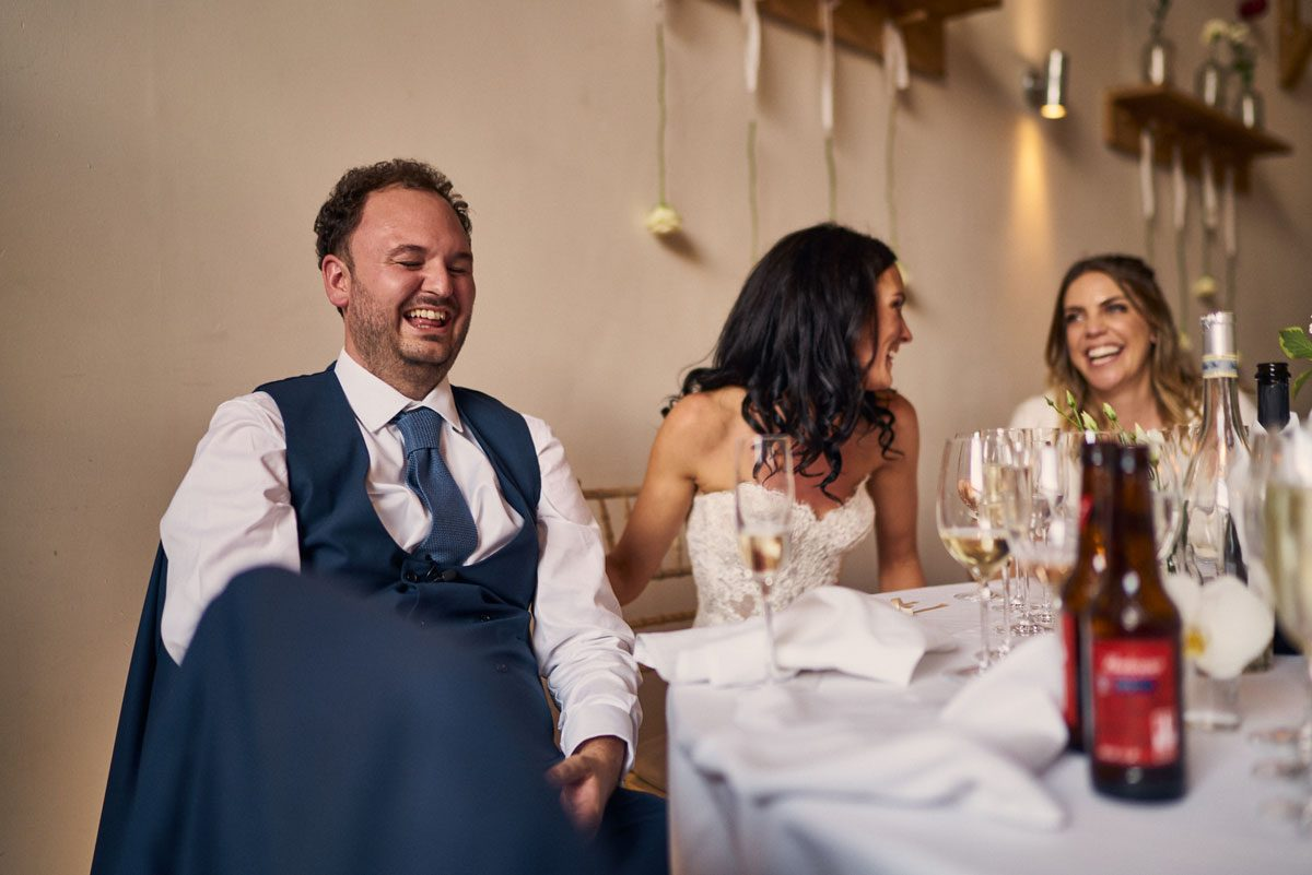 Bride & Groom laughing at wedding speeches