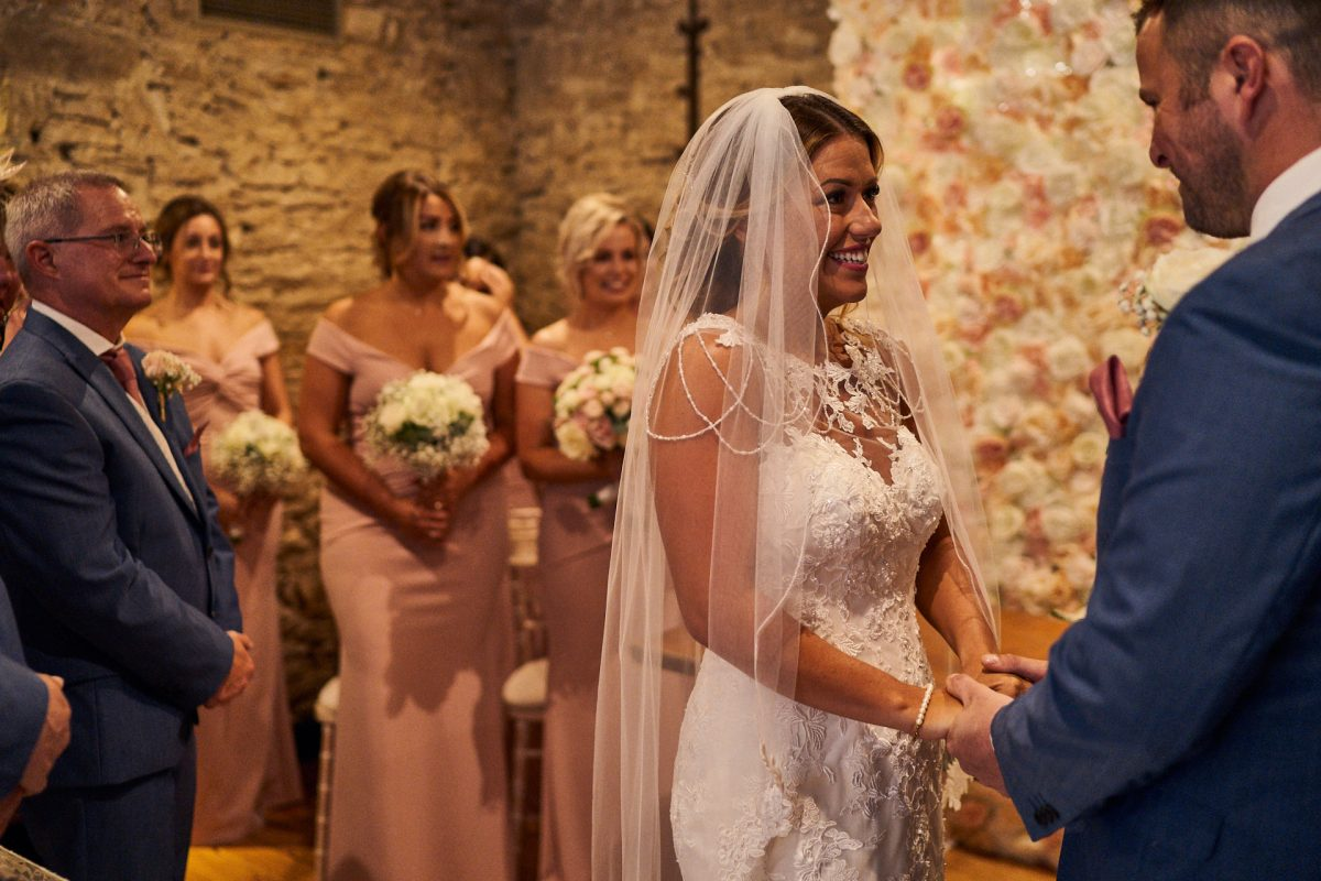 bride holding hand with groom during Great Tythe Barn wedding ceremony