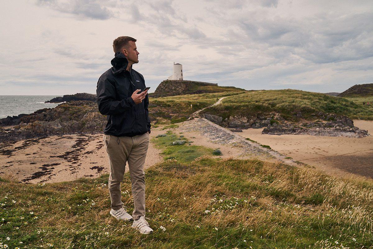 boyfriend waiting to surprise his girlfriend with a proposal on llanddwyn Island