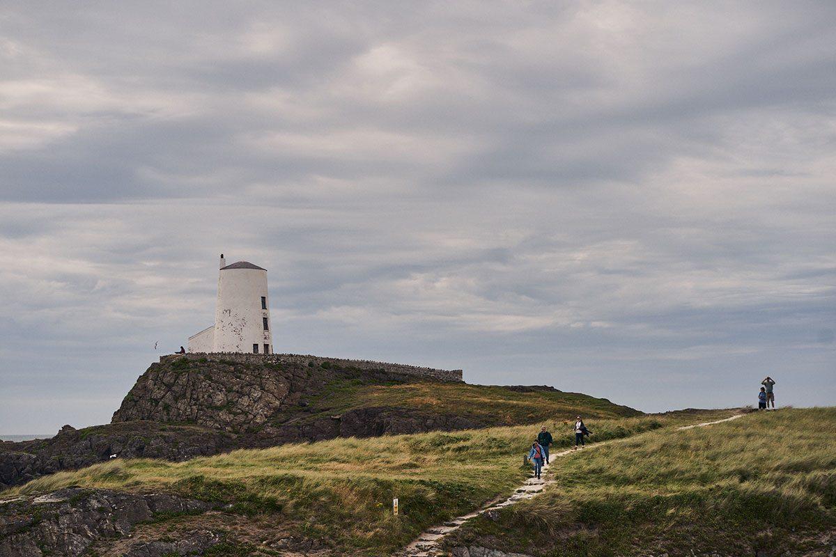 girlfriend approaching the surprise proposal location on Llanddwyn Island