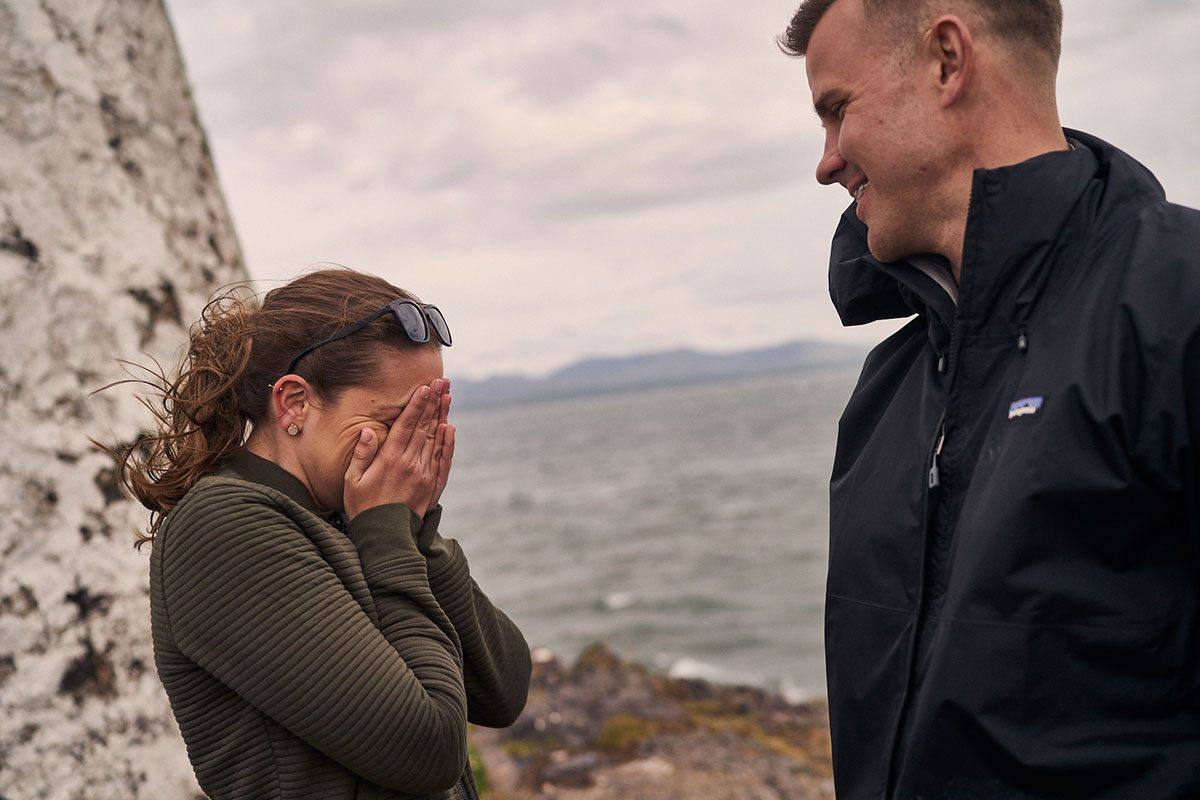 girlfriend covering her face in shock after surprise proposal