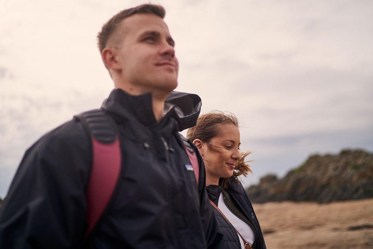 newly engaged couple smiling and happy on Newborough Beach