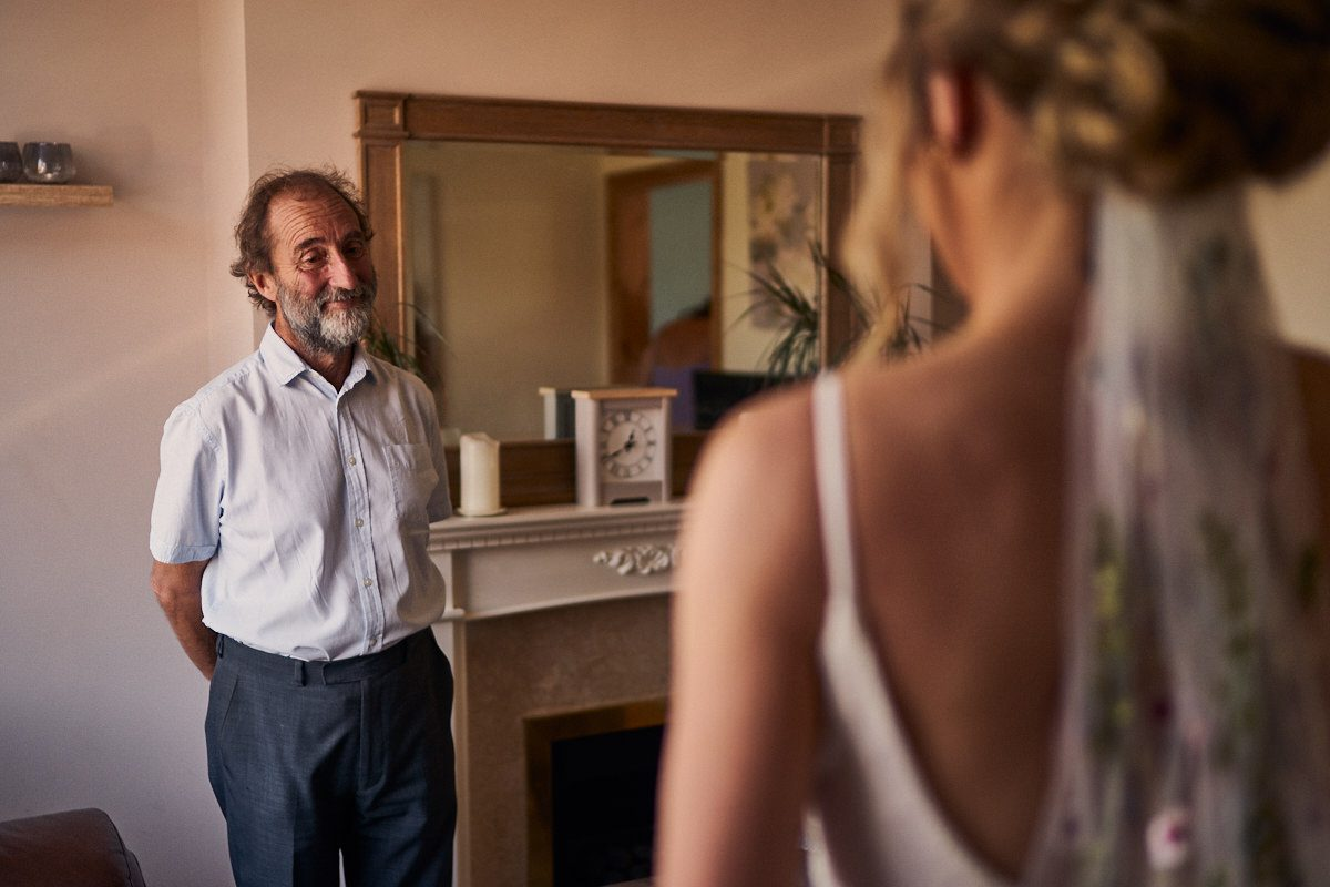 dad smiling at seeing his daughter in her wedding dress for the first time
