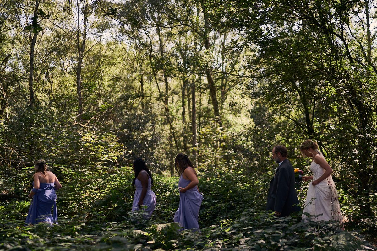 bride, father of the bride and bridesmaids walking through the forest to their outdoor wedding ceremony