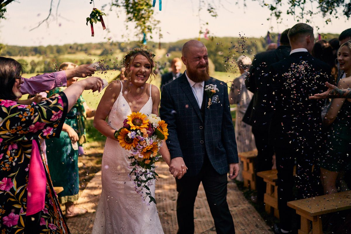 guests throwing confetti at bride and groom