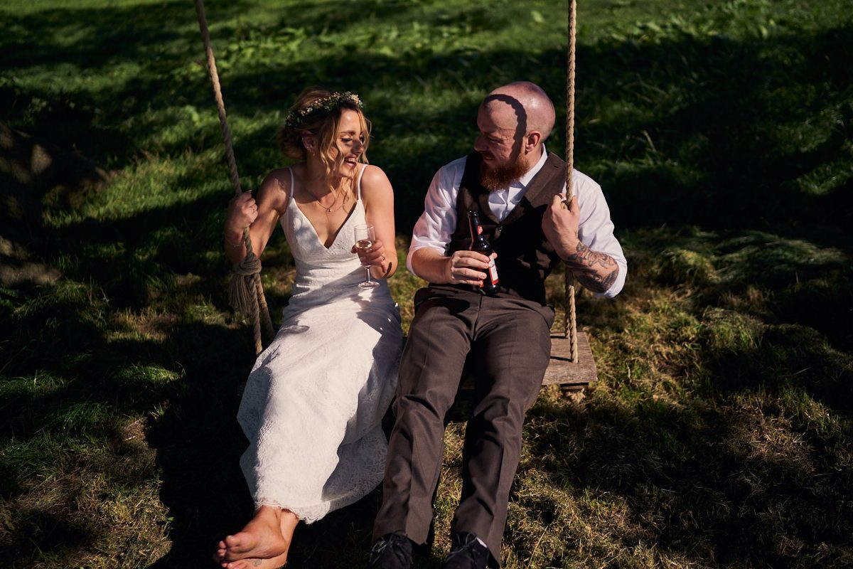 barefoot bride and groom laughing on swing