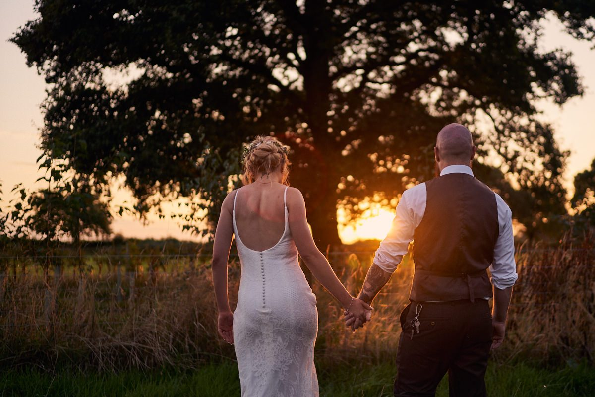 bride and groom walking off into the sunset