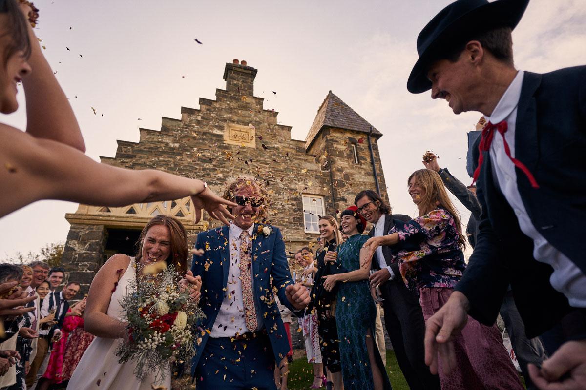 Weddings guests throwing confetti at Bride & Groom