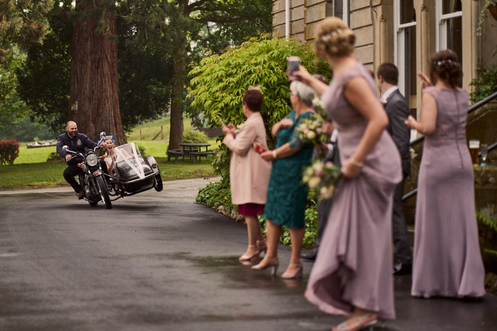 Bride doing a wheelie in a motorbike with side car - great alternative wedding day transport