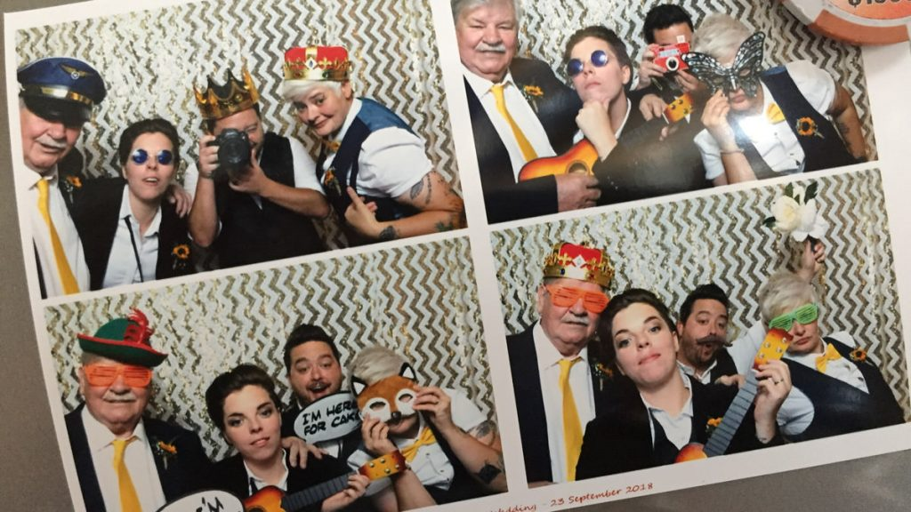 couple having selfie taken with their wedding photographer in a Photo Booth.