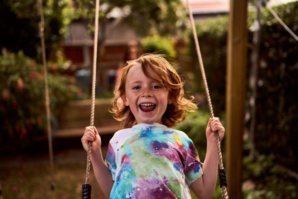 child smiling on back garden swing