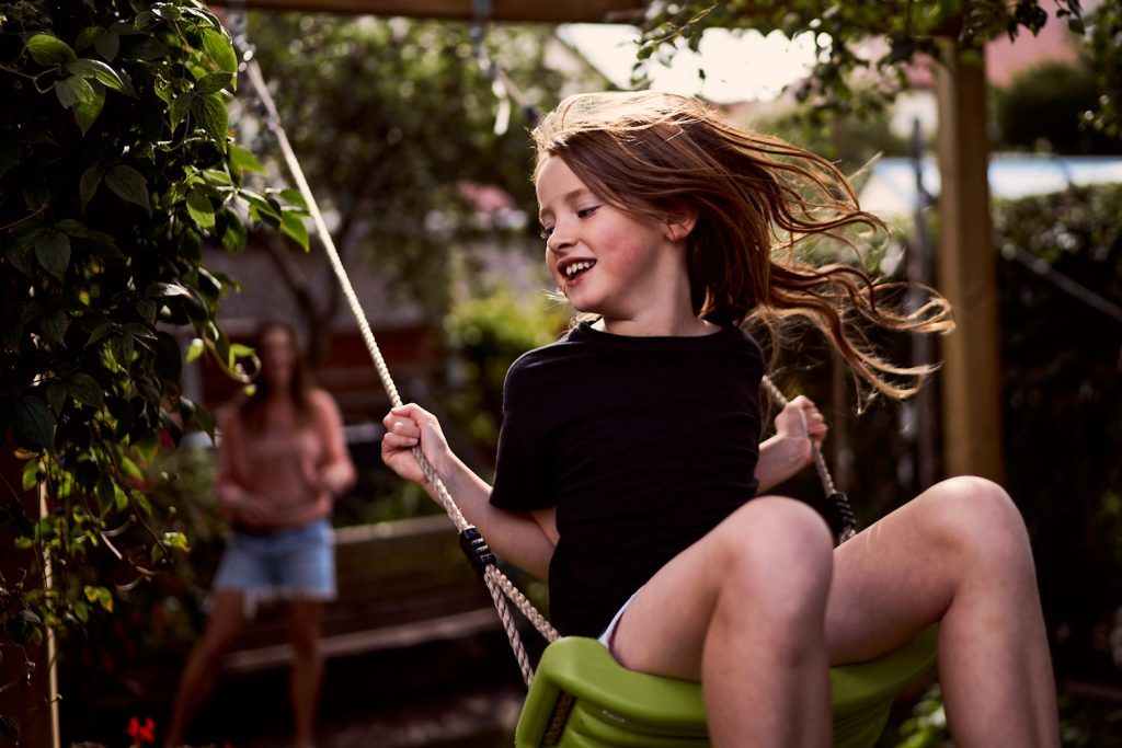 young girl smiling on back garden swing
