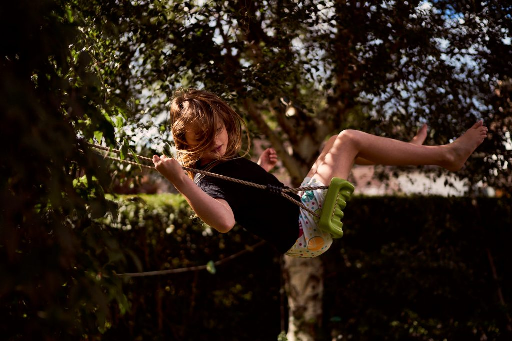 girl swinging on swing with hair in her face