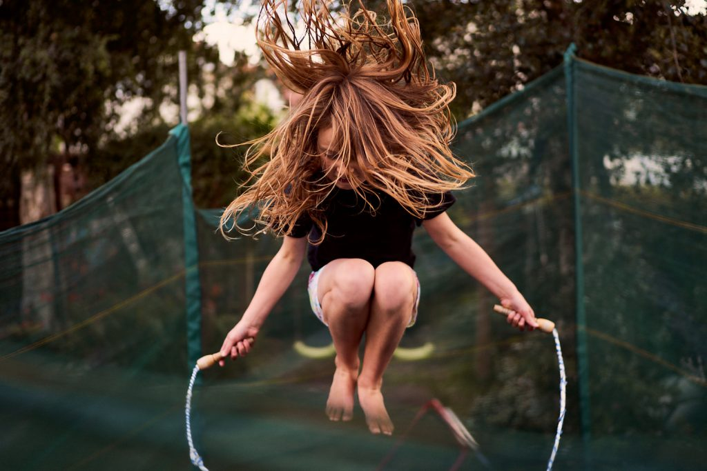 girl skipping while on trampoline