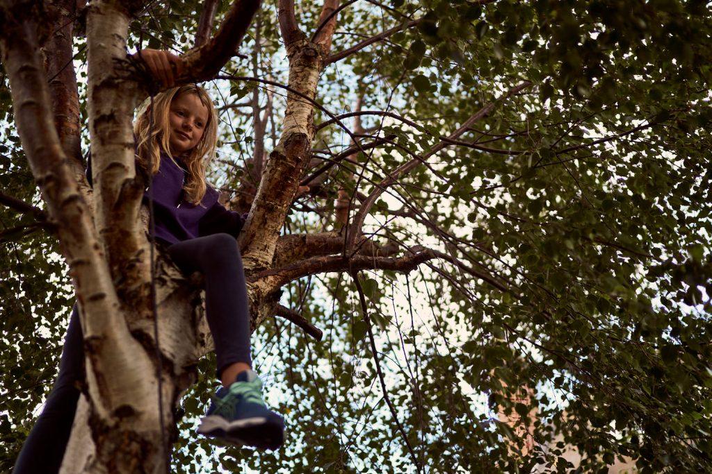 girl climbing tree in her back garden