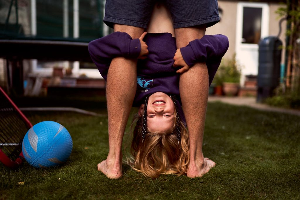 dad holding his daughter upside down by her feet