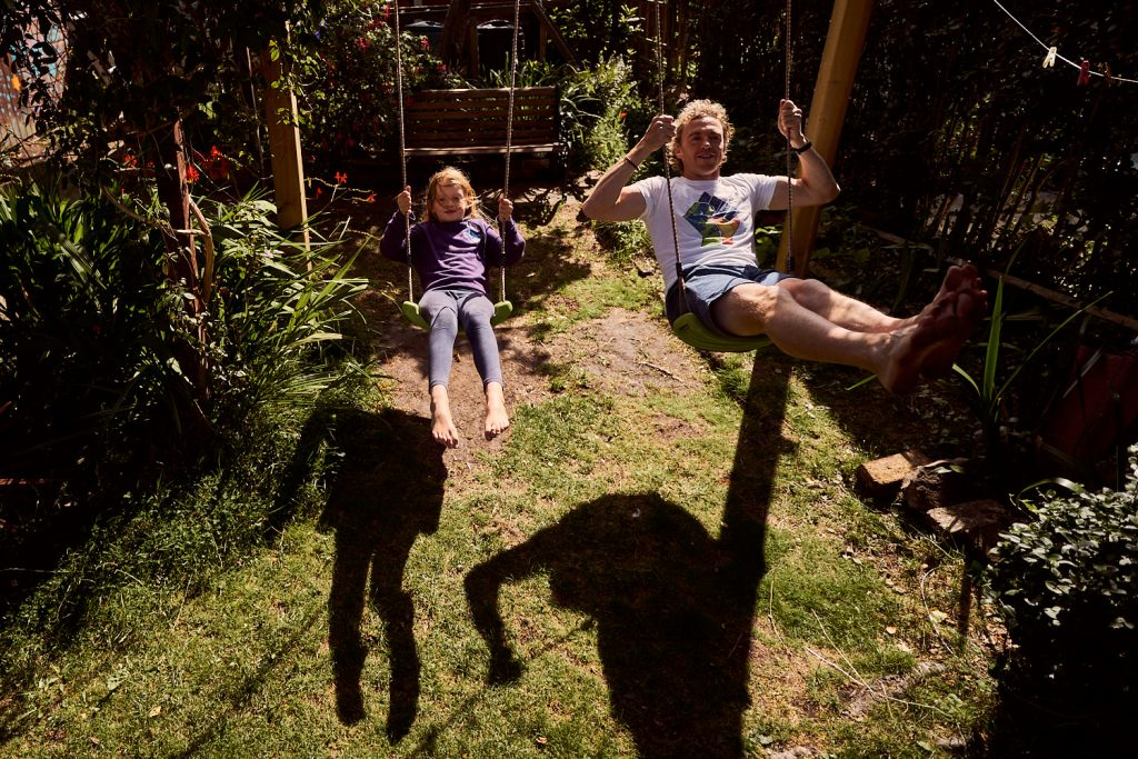 dad and daughter playing on the swings in their garden