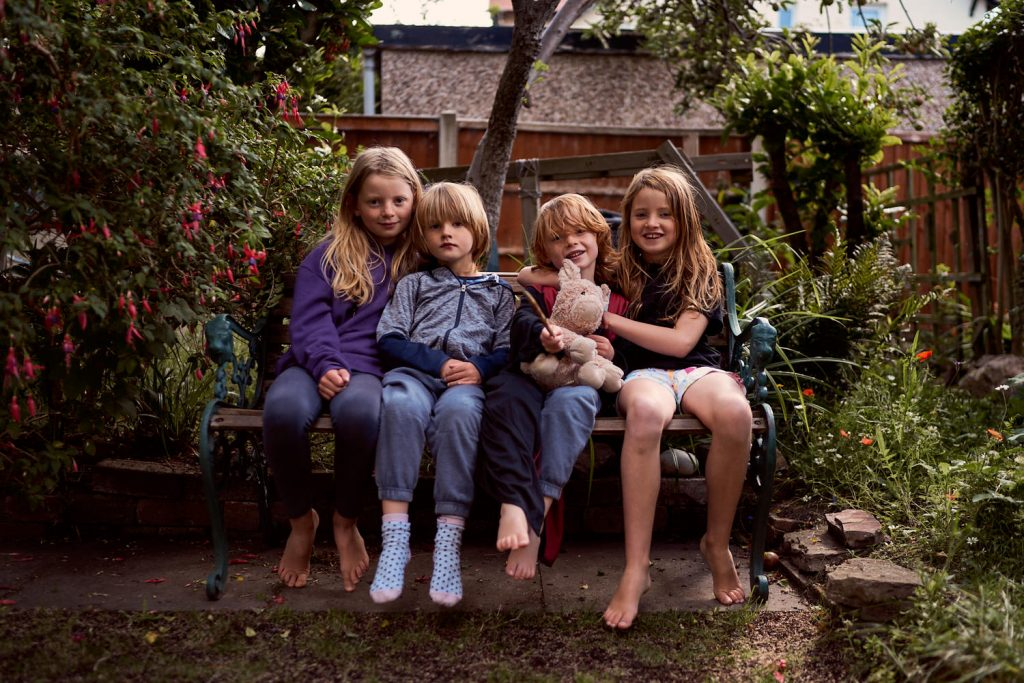 brothers and sisters sat on a bench