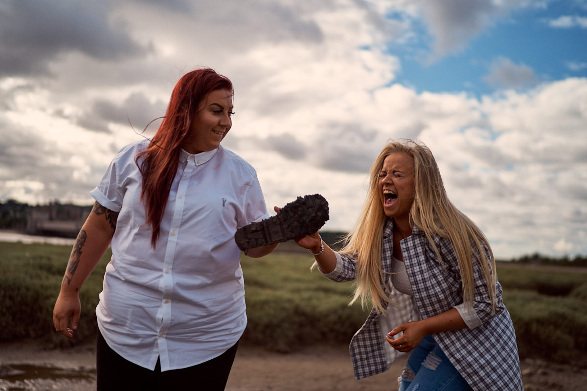 girl laughing at her girlfriend who lost her shoe in the mud