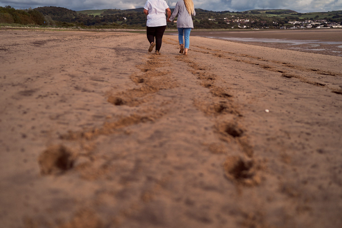 newly engaged couple walking back along the sand