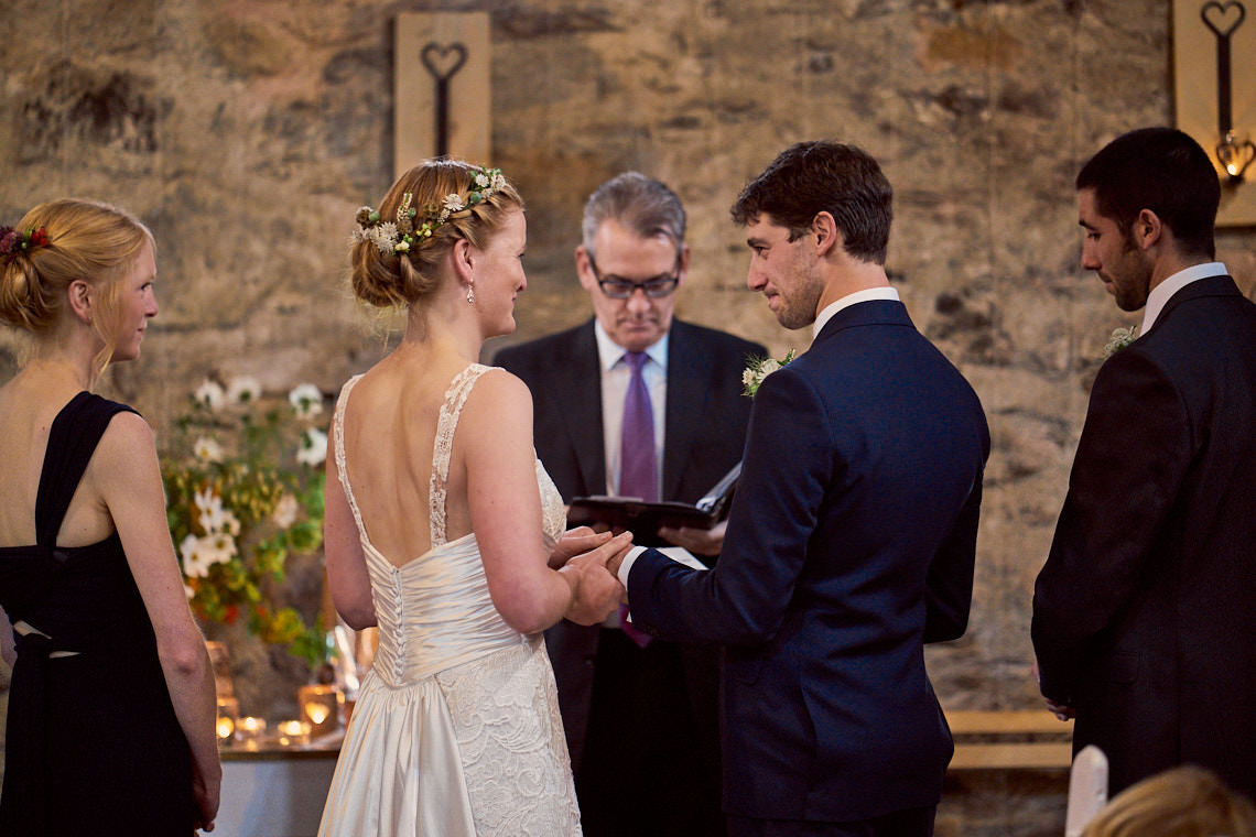 husband and wife exchanging rings in Hafod Farm's Wedding Barn