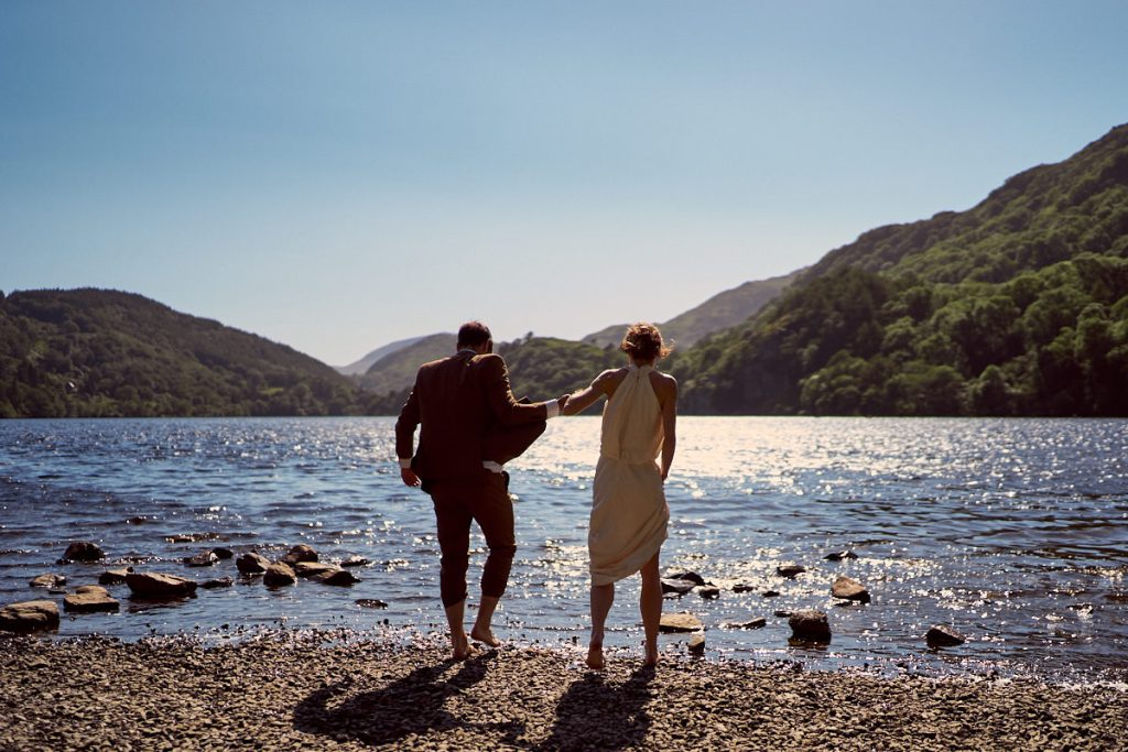 Newly weds having a paddle in a lake at the bottom of Mount Snowdon
