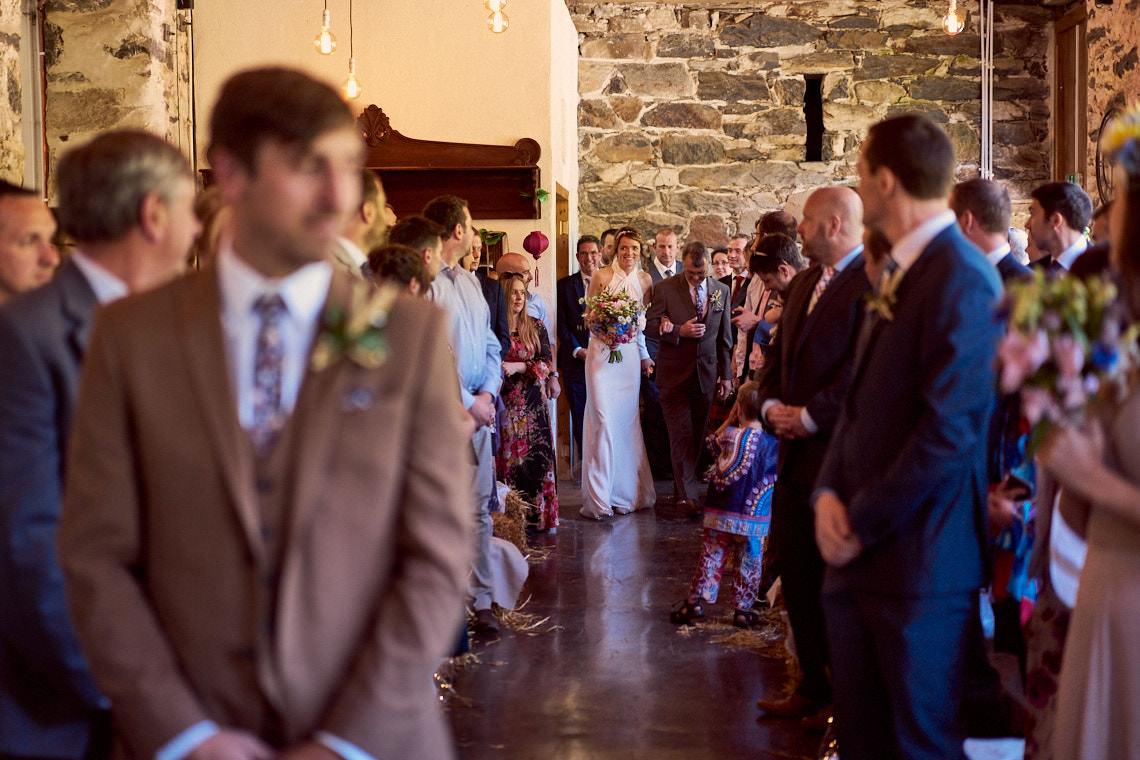 bride walking down the aisle at Llyn Gwynant Barns