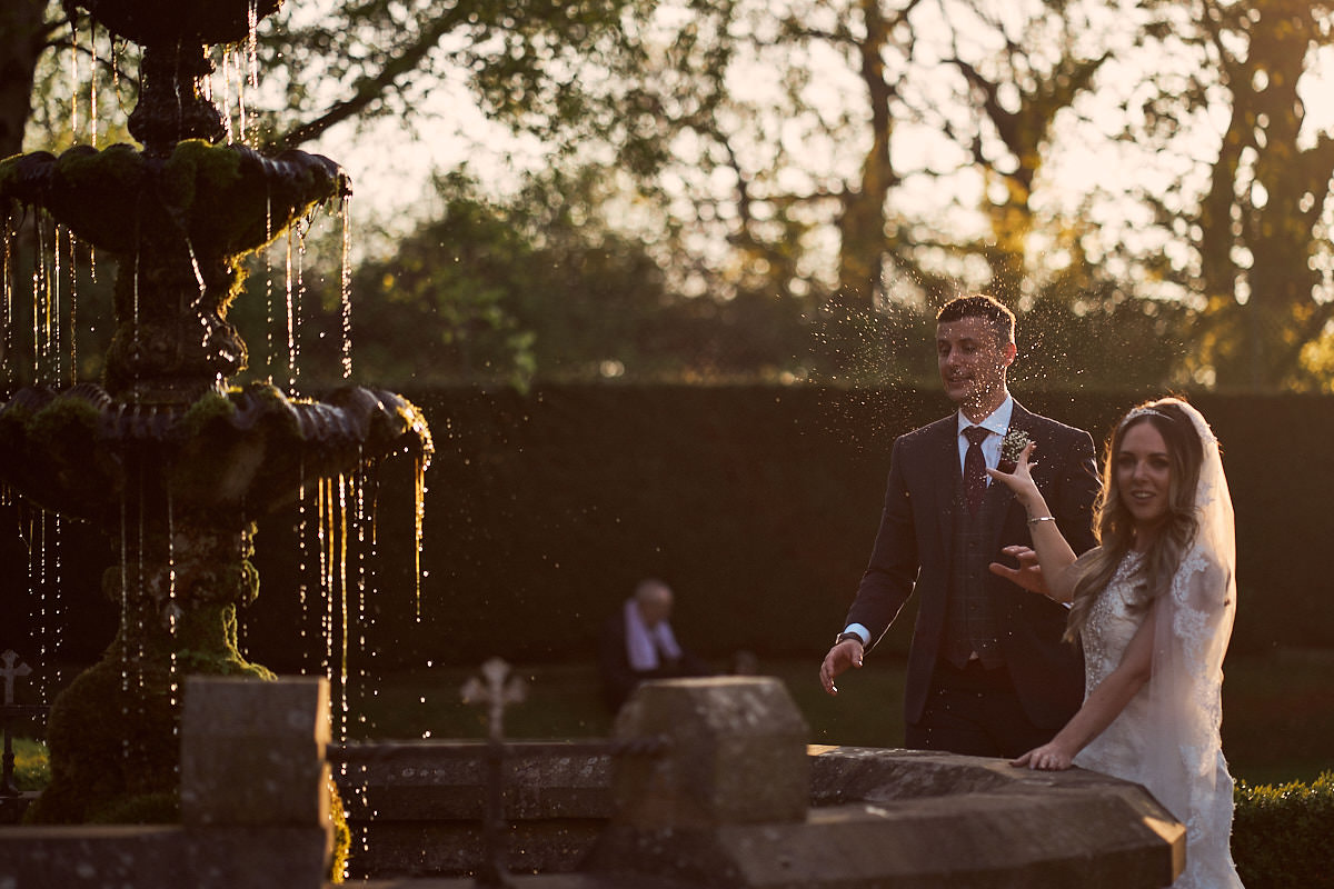 bride splashing groom with water from a fountain in Soughton Hall gardens