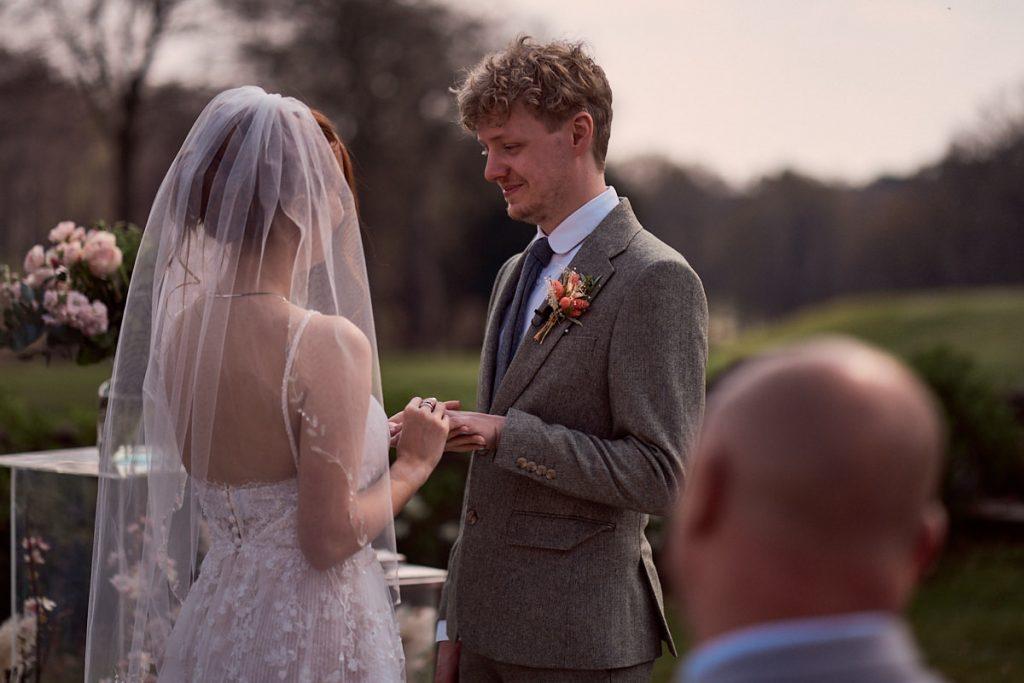 bride putting her wedding ring on her husbands finger