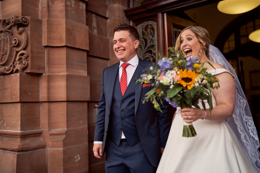bride and groom smiling as they leave Altrincham town hall