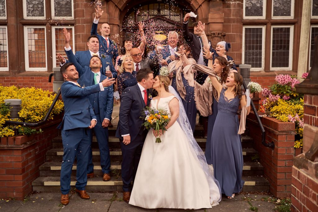 bride and groom with confetti on the steps of Altrincham hall