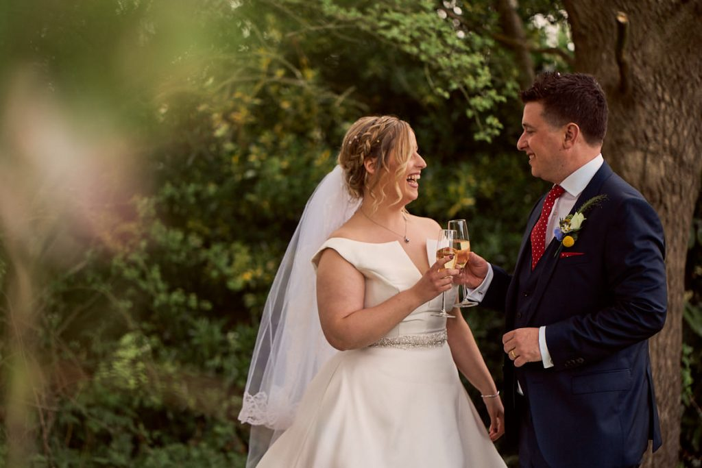 Newly married couple having champagne in the garden